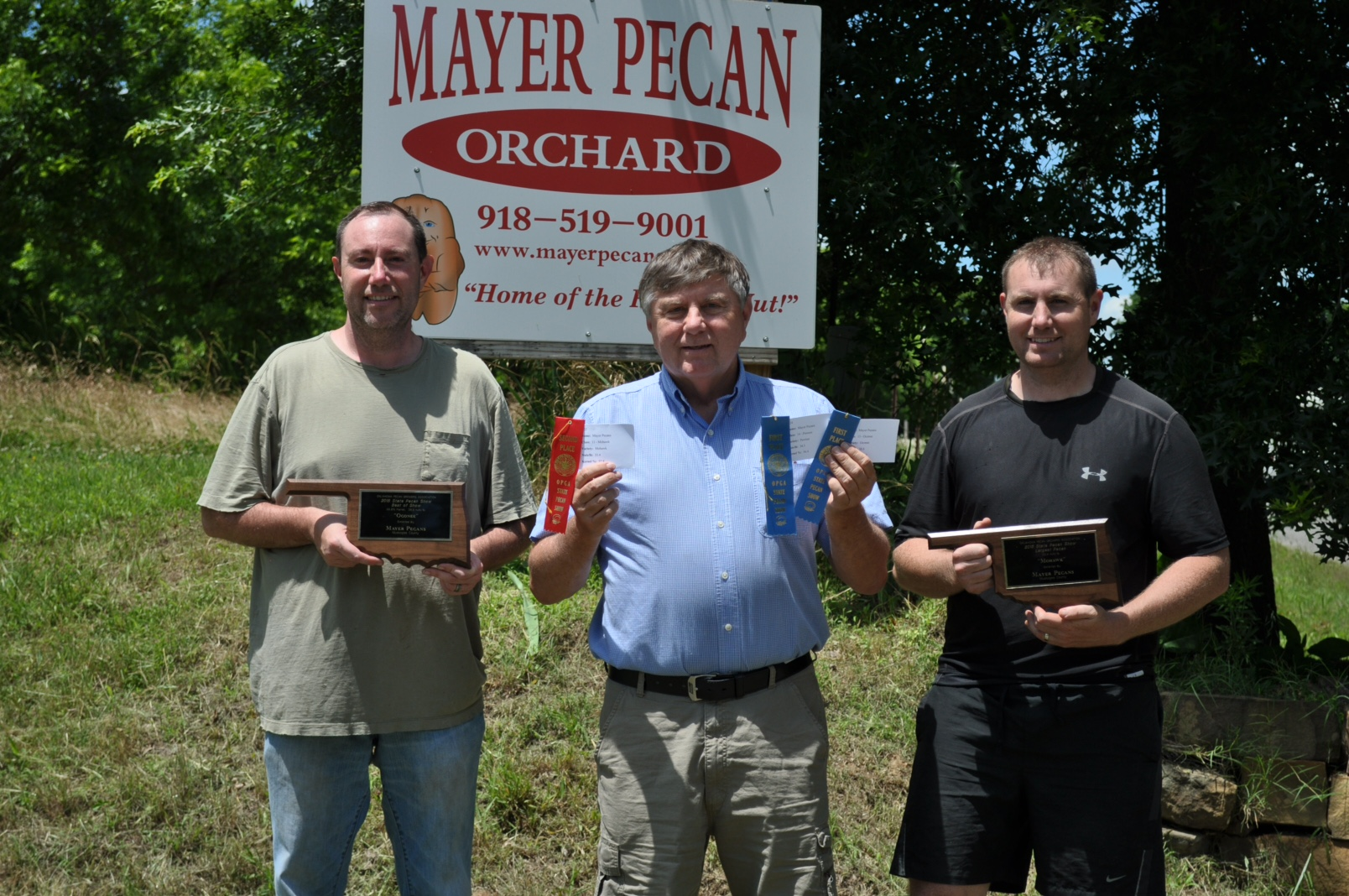 picture of Mayer Pecan Orchard with all their awards won at the 2018 Oklahoma Pecan Growers Association Convention. 1st Place Pawnee Pecan, 1st Place Oconee Pecan, 2nd Place Mohawk Pecan, Best in Show, Largest Pecan